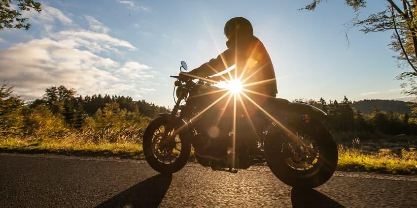 motorbiker on sunlit road